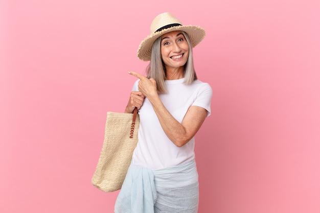 興奮して驚いた中年の白髪の女性が横を指しています。夏のコンセプト