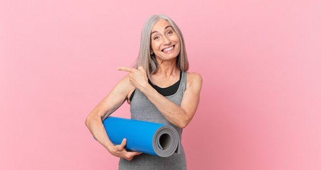 Middle age white hair woman looking excited and surprised pointing to the side and holding a yoga mat. fitness concept
