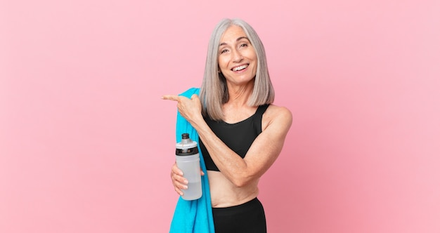 Middle age white hair woman looking excited and surprised pointing to the side with a towel and water bottle. fitness concept