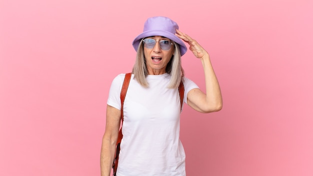 Middle age white hair woman looking happy, astonished and surprised. summer concept