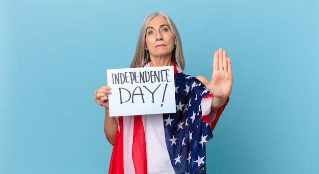 真剣に見える中年の白髪の女性は、開いた手のひらを停止ジェスチャーを示しています。独立記念日のコンセプト