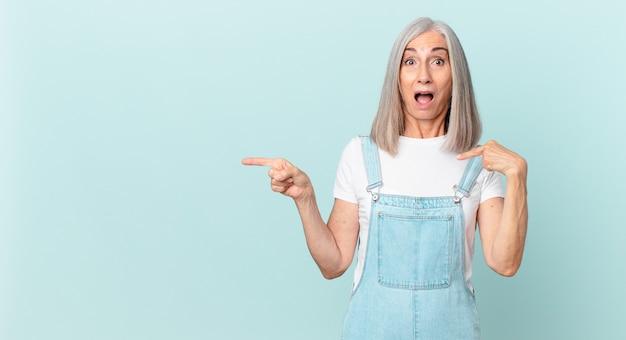 中年の白髪の女性は、口を大きく開いて、自分を指して、横を指して、ショックを受けて驚いたように見えます