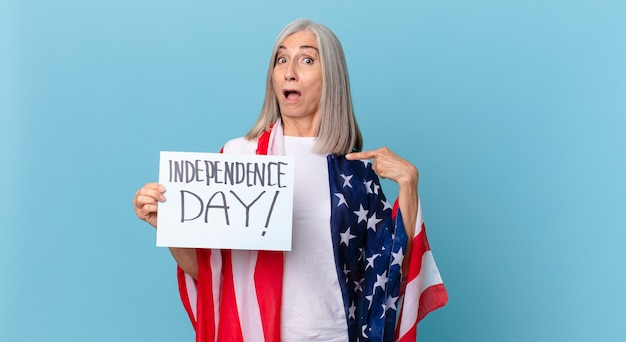 中年の白髪の女性は、口を大きく開けてショックを受けて驚いたように見え、自分を指しています。独立記念日のコンセプト