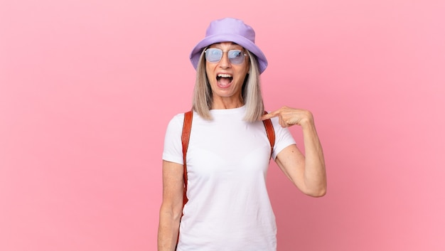 中年の白髪の女性は、口を大きく開けてショックを受けて驚いたように見え、自分を指しています。夏のコンセプト