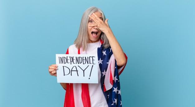 手で顔を覆って、ショックを受けたり、怖がったり、おびえたりしている中年の白髪の女性。独立記念日のコンセプト