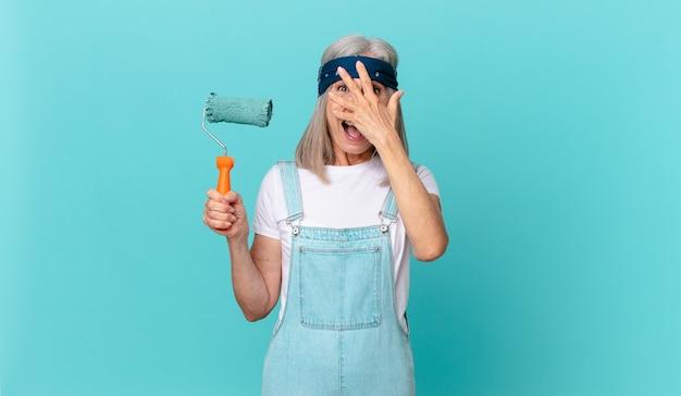 ショックを受けたり、怖がったり、恐怖を感じたり、壁を塗るローラーで顔を手で覆っている中年の白髪の女性