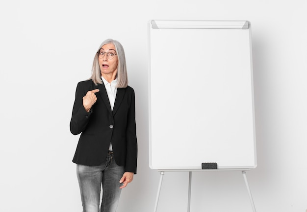 Middle age white hair woman looking shocked and surprised with mouth wide open, pointing to self and a board copy space. business concept