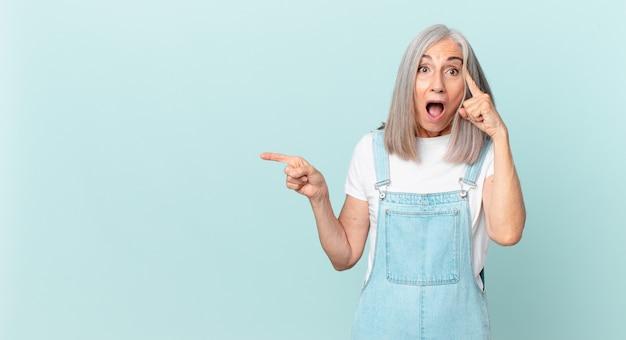 驚いた中年の白髪の女性は、新しい考え、アイデア、または概念を実現し、側を指しています