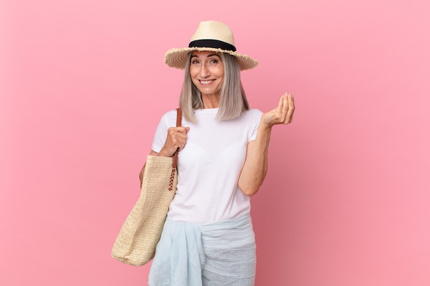 中年の白髪の女性が、お金を払うように言って、capiceまたはmoneyジェスチャーをします。夏のコンセプト