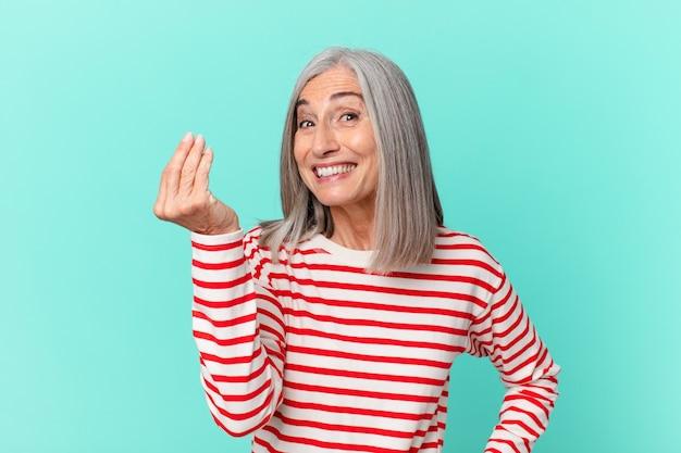 中年の白髪の女性がcapiceまたはお金のジェスチャーをして、あなたに支払うように言っています