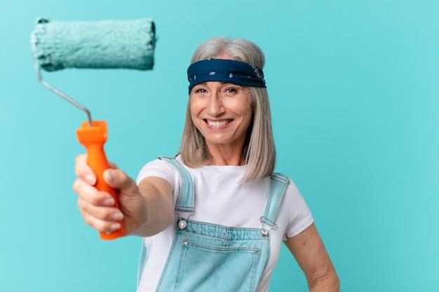 Женщина средних лет с белыми волосами красит стену