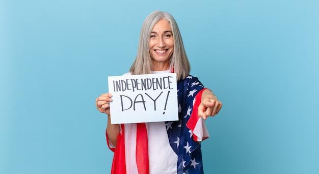 あなたを選ぶカメラを指している中年の白髪の女性。独立記念日のコンセプト