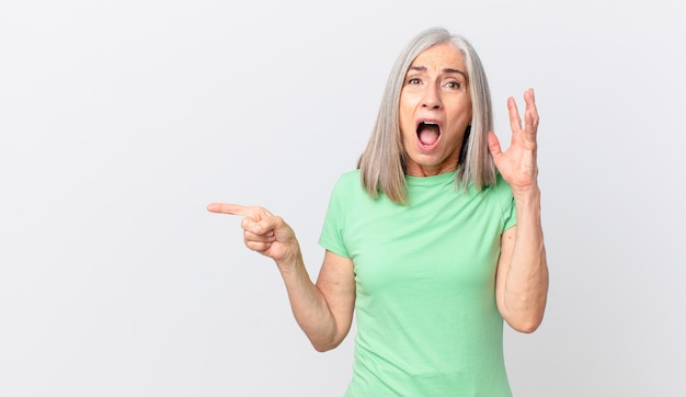 Middle age white hair woman screaming with hands up in the air and pointing to the side