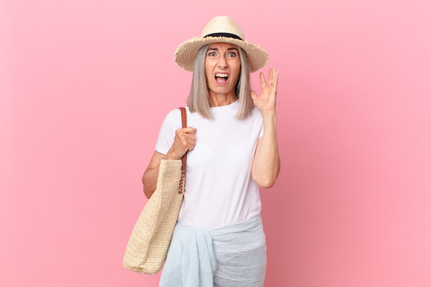 Middle age white hair woman screaming with hands up in the air. summer concept