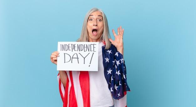 空中で手を上げて叫んでいる中年の白髪の女性。独立記念日のコンセプト