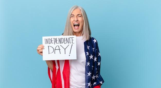 中年の白髪の女性が激しく叫び、非常に怒っているように見えます。独立記念日のコンセプト