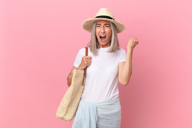 怒りの表情で積極的に叫ぶ中年白髪の女性。夏のコンセプト