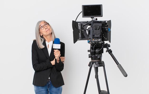 Женщина средних лет с белыми волосами пожимает плечами, чувствуя смущение и неуверенность, и держит микрофон. концепция телеведущего