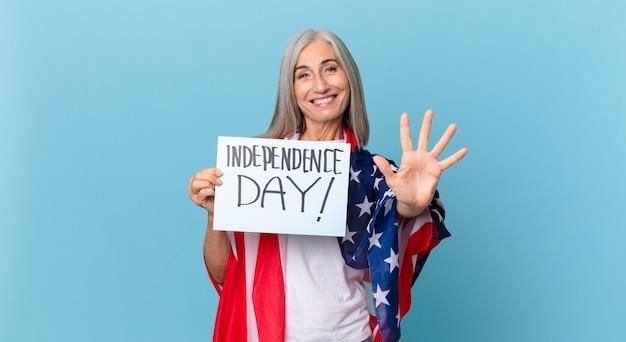 中年の白髪の女性が笑顔でフレンドリーに見え、5番を示しています。独立記念日のコンセプト