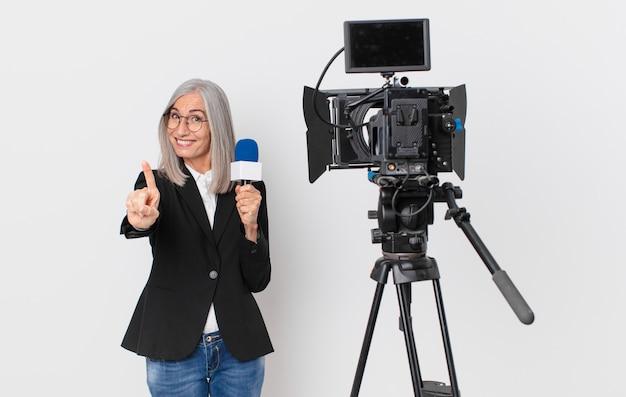 Женщина средних лет с белыми волосами улыбается и выглядит дружелюбно, показывает номер один и держит микрофон. концепция телеведущего