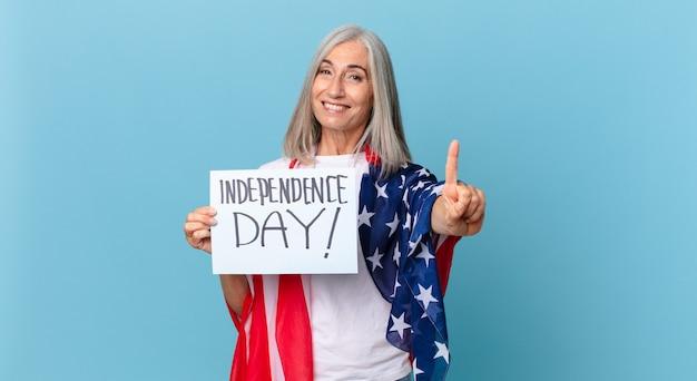 中年の白髪の女性が笑顔でフレンドリーに見え、ナンバーワンを示しています。独立記念日のコンセプト