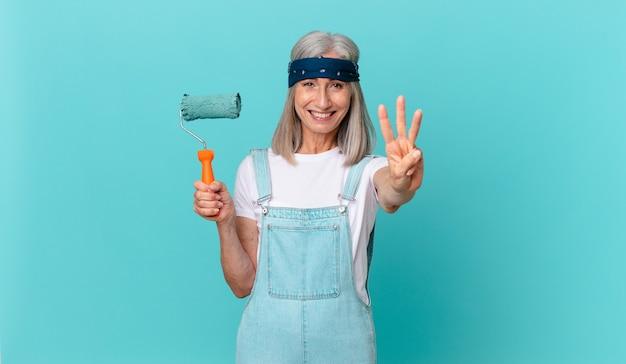 Женщина средних лет с белыми волосами улыбается и выглядит дружелюбно, показывая номер три с роликом, раскрашивающим стену