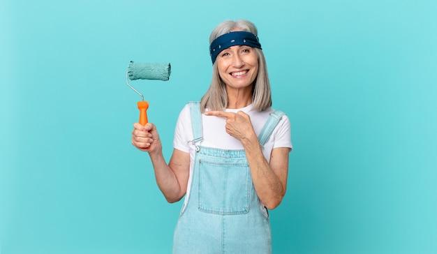 Среднего возраста женщина с белыми волосами весело улыбается, чувствует себя счастливой и указывает в сторону с роликом, раскрашивающим стену
