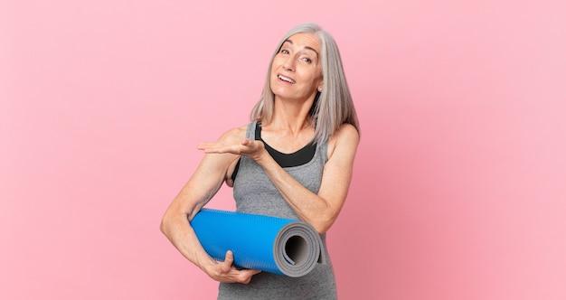 중년의 백발 여성은 즐겁게 웃고 행복하고 개념을 보여주고 요가 매트를 들고 있습니다. 피트니스 개념