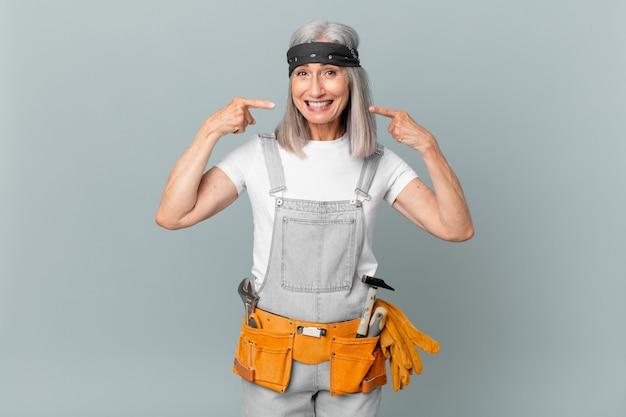 Среднего возраста женщина с белыми волосами уверенно улыбается, указывая на собственную широкую улыбку и носит рабочую одежду и инструменты. концепция домашнего хозяйства