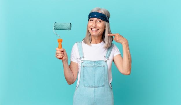 Среднего возраста женщина с белыми волосами уверенно улыбается, указывая на собственную широкую улыбку с роликом, раскрашивающим стену