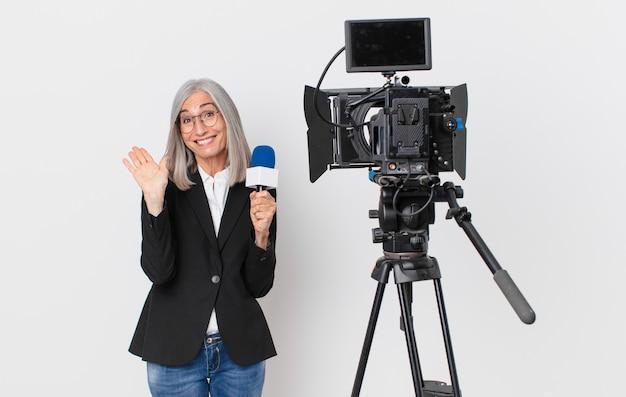Женщина средних лет с белыми волосами счастливо улыбается, машет рукой, приветствует и приветствует вас и держит микрофон. концепция телеведущего