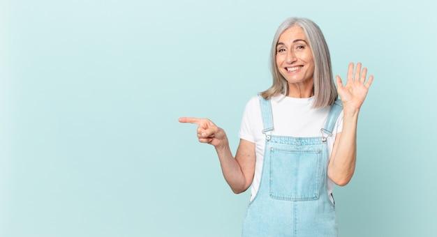 중년의 흰 머리 여성이 행복하게 웃고 손을 흔들며 환영하고 인사하고 옆을 가리키며