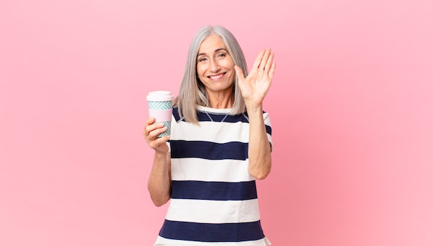 Middle age white hair woman smiling happily, waving hand, welcoming and greeting you and holding a take away coffee container