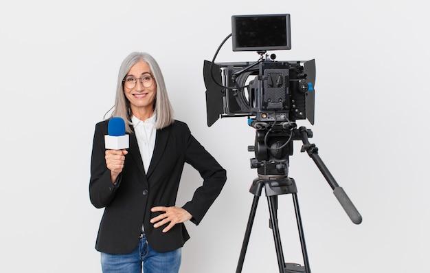 Женщина средних лет с белыми волосами, счастливо улыбается, положив руку на бедро и уверенно и держа микрофон. концепция телеведущего