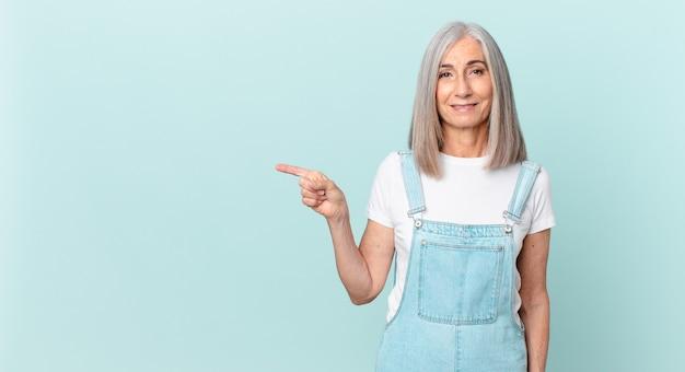 腰に手を当てて幸せそうに笑って自信を持って横を向いている中年白髪の女性