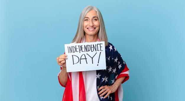腰に手を当てて幸せそうに笑って自信を持っている中年白髪の女性。独立記念日のコンセプト Premium写真