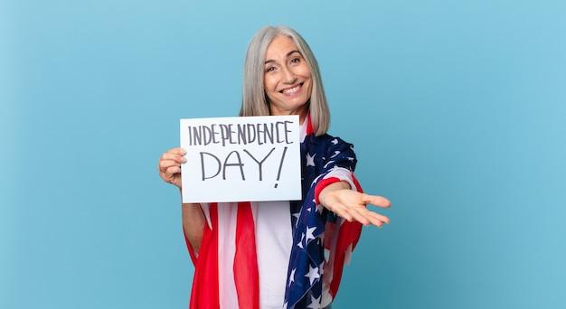 中年の白髪の女性は、フレンドリーで幸せに笑って、コンセプトを提供し、示しています。独立記念日のコンセプト