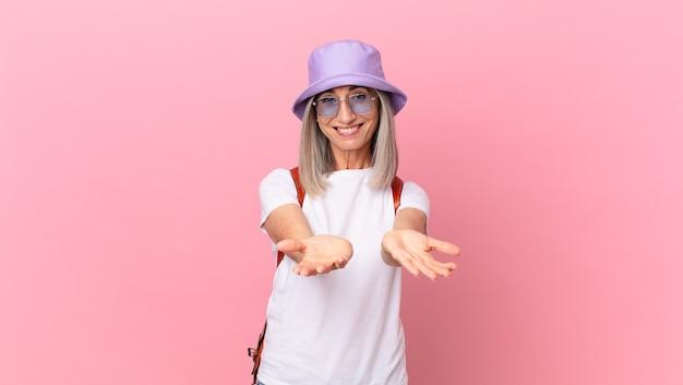 中年の白髪の女性は、フレンドリーで幸せに笑って、コンセプトを提供し、示しています。夏のコンセプト
