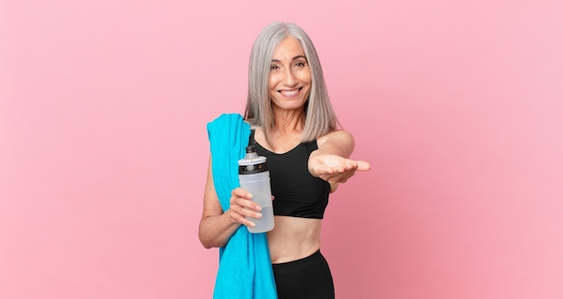 Женщина средних лет с белыми волосами счастливо улыбается, дружелюбно предлагает и показывает концепцию с полотенцем и бутылкой с водой. фитнес-концепция