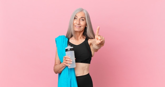 Middle age white hair woman smiling and looking friendly, showing number one with a towel and water bottle. fitness concept