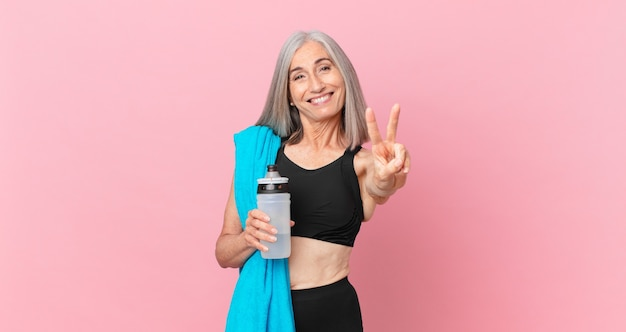 Middle age white hair woman smiling and looking friendly, showing number two with a towel and water bottle. fitness concept