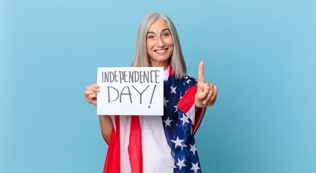 Женщина средних лет с белыми волосами, гордо и уверенно улыбаясь, делает номер один. концепция дня независимости