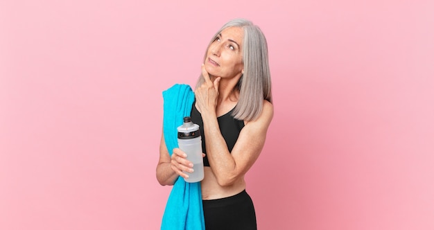 Middle age white hair woman smiling with a happy, confident expression with hand on chin with a towel and water bottle. fitness concept