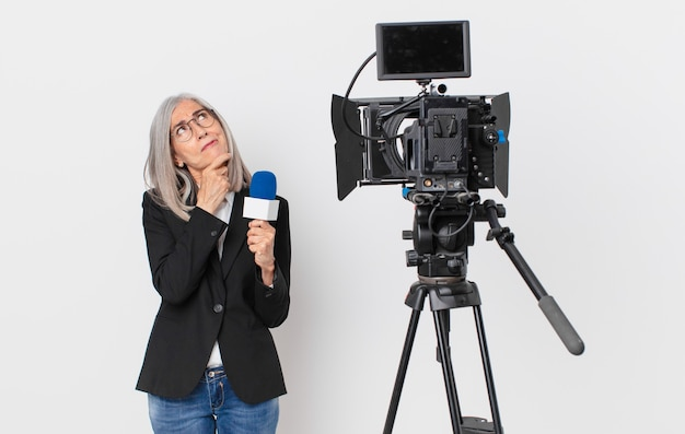 Middle age white hair woman thinking, feeling doubtful and confused and holding a microphone. television presenter concept