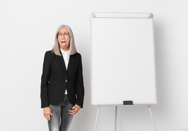 Middle age white hair woman with cheerful and rebellious attitude, joking and sticking tongue out and a board copy space. business concept