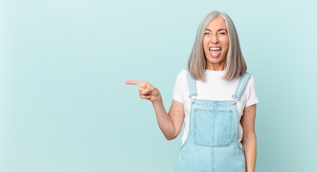 Middle age white hair woman with cheerful and rebellious attitude, joking and sticking tongue out and pointing to the side