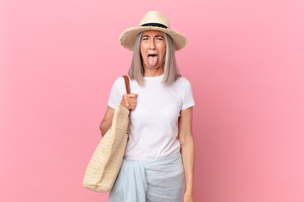 Middle age white hair woman with cheerful and rebellious attitude, joking and sticking tongue out. summer concept