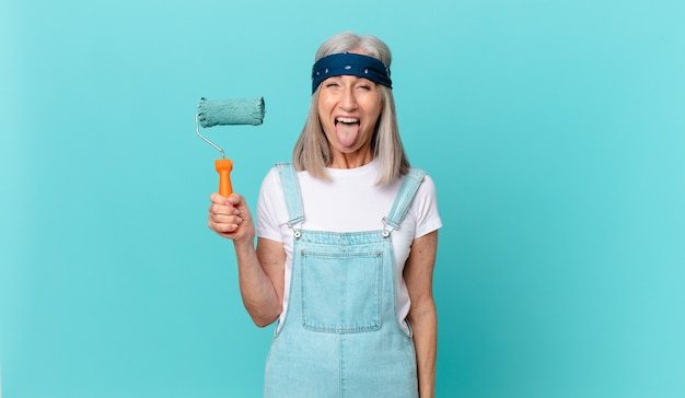Middle age white hair woman with cheerful and rebellious attitude, joking and sticking tongue out with a roller painting a wall