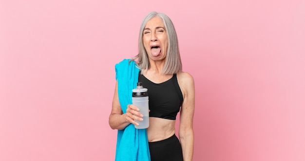 Middle age white hair woman with cheerful and rebellious attitude, joking and sticking tongue out with a towel and water bottle. fitness concept