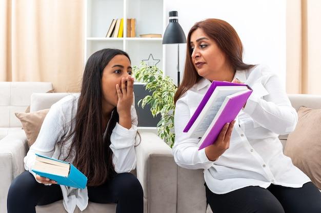 中年の女性と白いシャツを着た若い娘と黒いズボンが本を持って椅子に座っている 明るいリビング ルームで本を見て驚いている娘